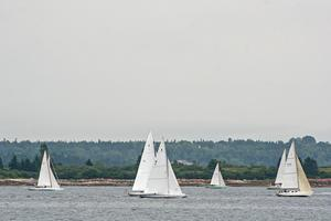 A fleet of vintage yachts sail through the Reach