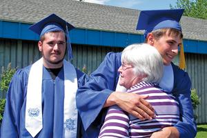 The Deer Isle-Stonington graduation receiving line  Deven Olsen looks on as Lucas Oliver gets a hug