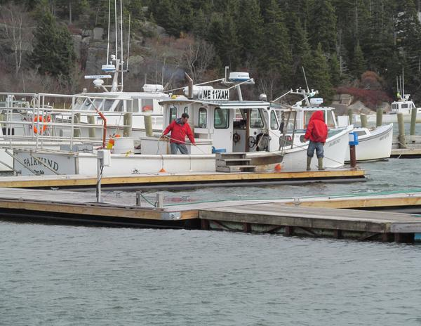 A boat's crew works to prepare the boat
