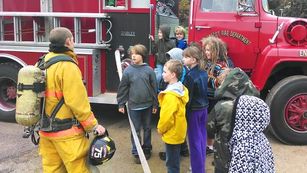 Penobscot students climb on Penobscot Fire Department trucks