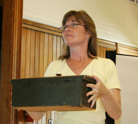 Karen Motycka holds up the ballot box at Castine Town Meeting