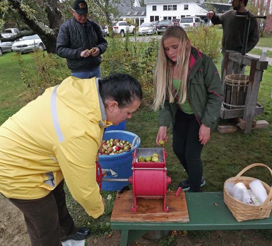 Rachel Chandler turns the wheel on the apple grinder