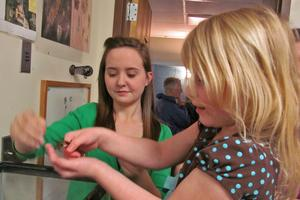 Megan Weed helps Emily West  check out a small creature