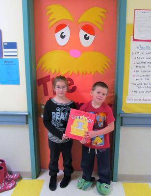 Riley Hayward and Owen Staples hold Gail Page's How to be a Good Cat