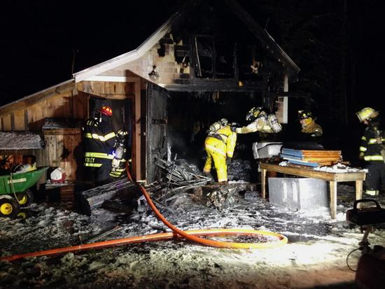 Firefighters peruse damage at the Moose Island home