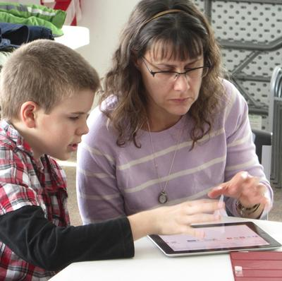 Brooksville, Maine student John Bakeman demonstrate iPad to Amber Bakeman