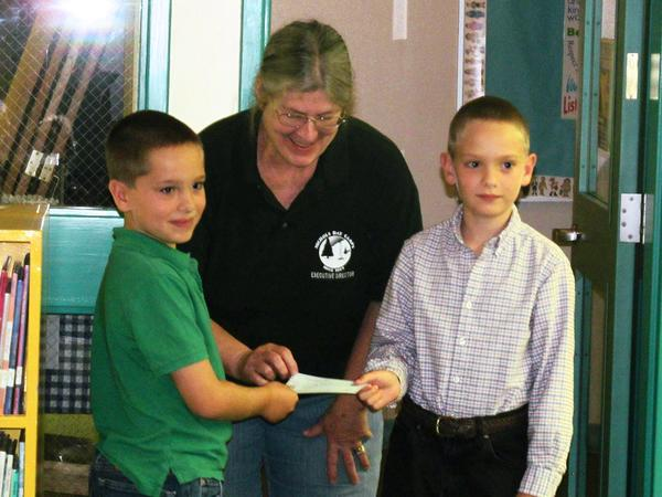 Logan and Emery Leach present Candy Eaton with a $5,000 donation from the Friends of Walker Pond