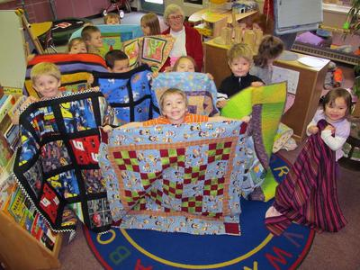 Hancock County Quilters present handmade quilts to students in Sedgwick