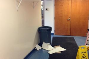 A garbage can catches leaks in a hall at Blue Hill Consolidated school