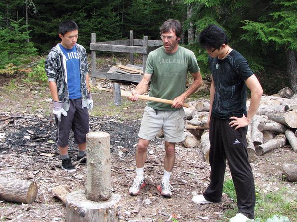 Peter Wu and Corey An chop wood with Matt Broughton