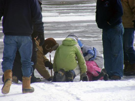 Kids gather around an ice fishing hole